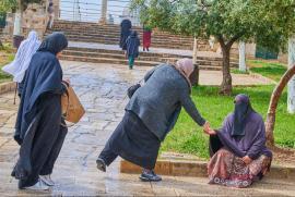 donna velata riceve l'elemosina alla spianata delle moschee di Gerusalemme