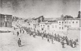 Armeni in marcia forzata verso il il campo di prigionia di Mezireh, sorvegliati da soldati turchi