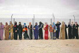 Donne siriane rifugiate in coda per ricevere il kit di aiuti per l'inverno nel campo di Zaatari, Giordania