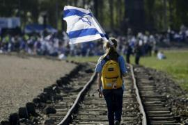 Una ragazza sventola la bandiera israeliana sugli ex binari di Birkenau