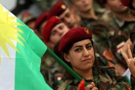 Una peshmerga curda porta la bandiera del suo Stato in costruzione