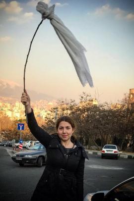 """Una giovane ragazza Iraniana protesta contro la """"hijab rule""""."""