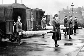 Donne che reggono delle barelle sul retro delle ambulanze durante l'epidemia mondiale d'influenza, St Louis, Missouri, ottobre 1918.