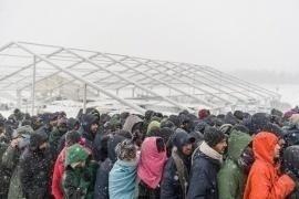 Migranti in fila per ricevere un pasto caldo distribuito dagli operatori della Croce rossa all'ingresso del campo profughi di Lipa, Bosnia, 8 gennaio 2021.