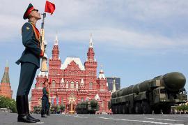 Soldato agita bandiera rossa davanti al Cremlino (foto di cyprusgasnews)