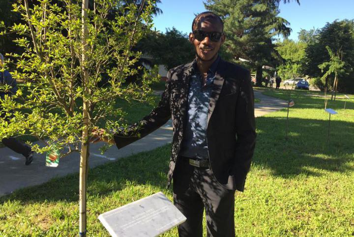 Lassana Bathily accanto all'albero in suo onore