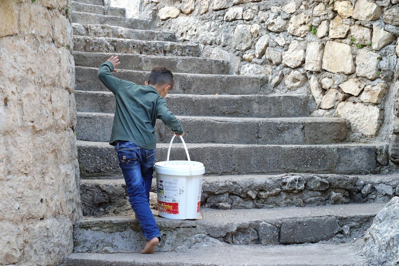 Bambino yazida che porta l'acqua sacra al tempio di Lalish