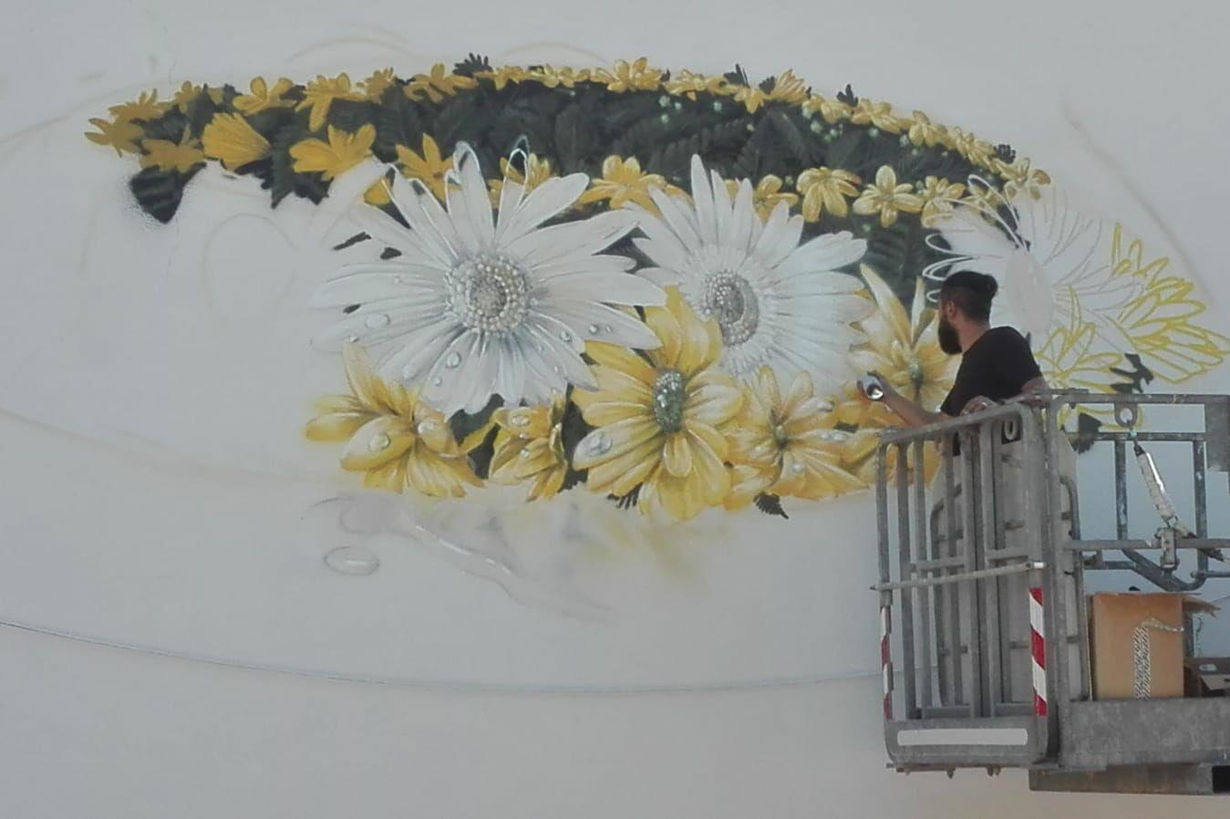L'artista Neve lavora al murales in piazza Piave