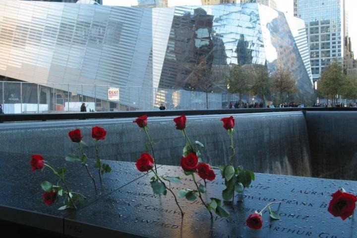 Rose infilate nelle lettere della targa commemorativa