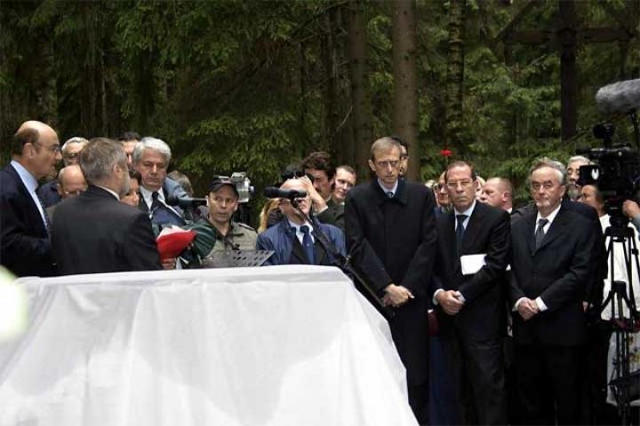 Le autorità e i parenti intorno alla stele coperta prima della cerimonia