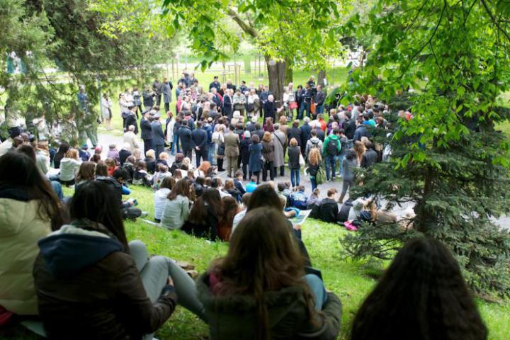 Un gruppo di studenti assiepato sul pendio del Monte Stella assistono alla Cerimonia