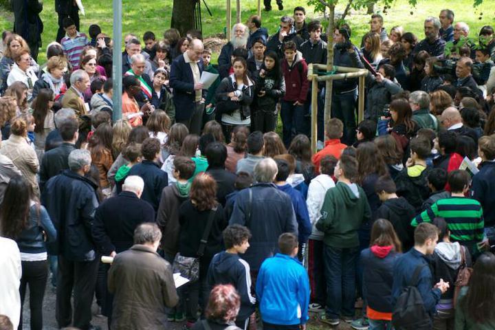 Yolande Mukagasana attorniata dagli studenti e dalle autorità parla accanto all'albero a lei dedicato