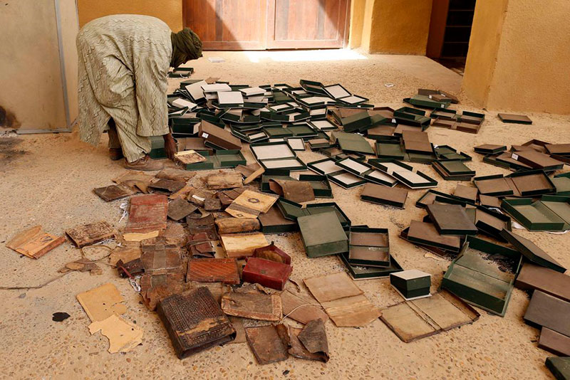 Una guardia dell'Istituto Ahmed Baba al lavoro attorno alle scatole che contenevano antichi manoscritti parzialmente danneggiati dal fuoco appiccato dai miliziani, 2013