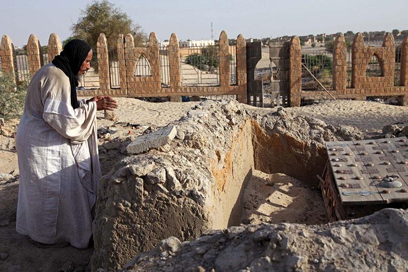 Un custode in preghiera su una tomba di Timbuktu danneggiata dai miliziani nel 2012.
