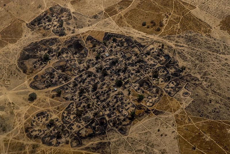 Un villaggio nigeriano incendiato visto da un elicottero delle Nazioni Unite in volo tra Maiduguri e Monguno, 2017.