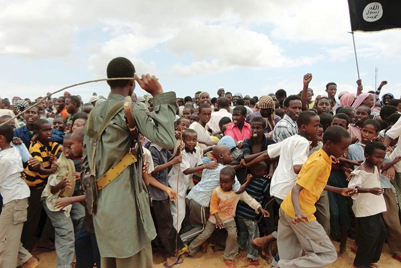Un membro di Al-Shabaab tiene sotto controllo la folla durante una manifestazione, 2011.