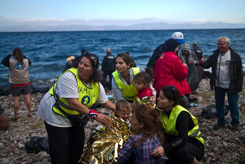 Volontari prestano i primi aiuti ai migranti.