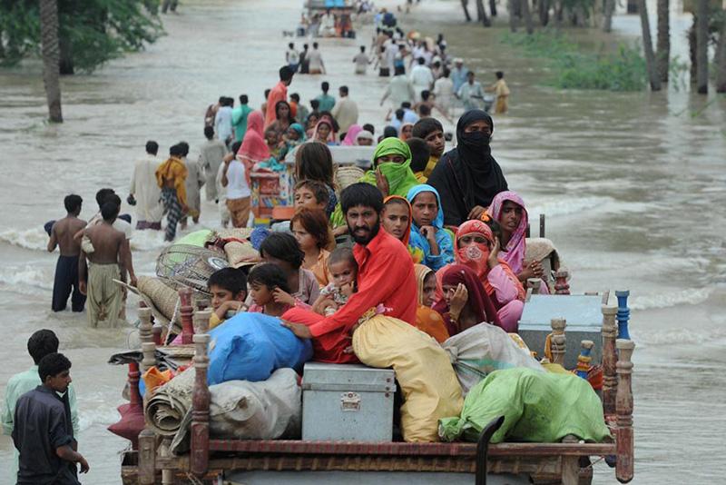 I sopravvissuti alle inondazioni pakistane evacuano un'area allagata.