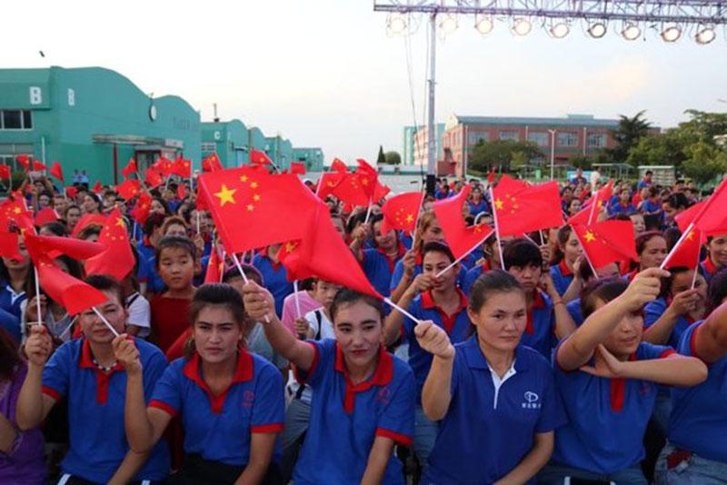 Lavoratrici uigure della Taekwang Shoe Manufacturing sventolano la bandiera cinese, ottobre 2019.