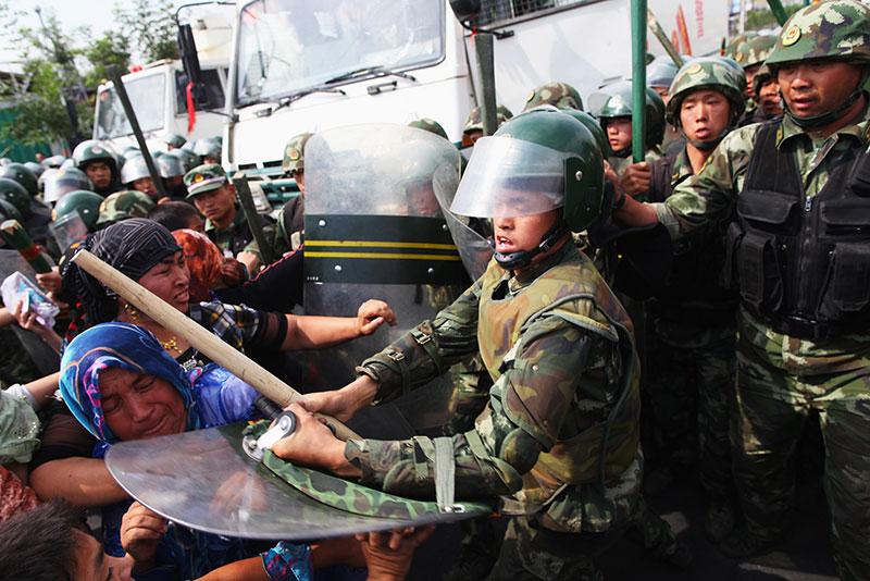 I poliziotti spingono le donne uigure che stanno protestando in strada il 7 luglio 2009 a Urumqi dopo che i loro parenti sono stati arrestati dalle autorità.
