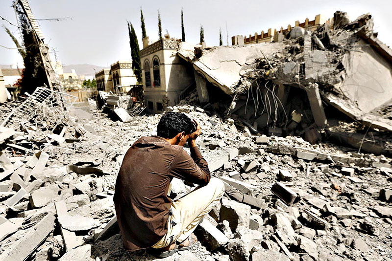 A guard sits on the rubble of the home of an army commander loyal to the Hauthi, after air raids destroyed it in Sanaa.